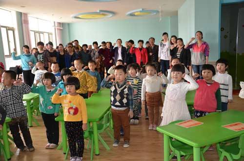 图为幼儿园的小朋友和家长一起宣誓反对浪费